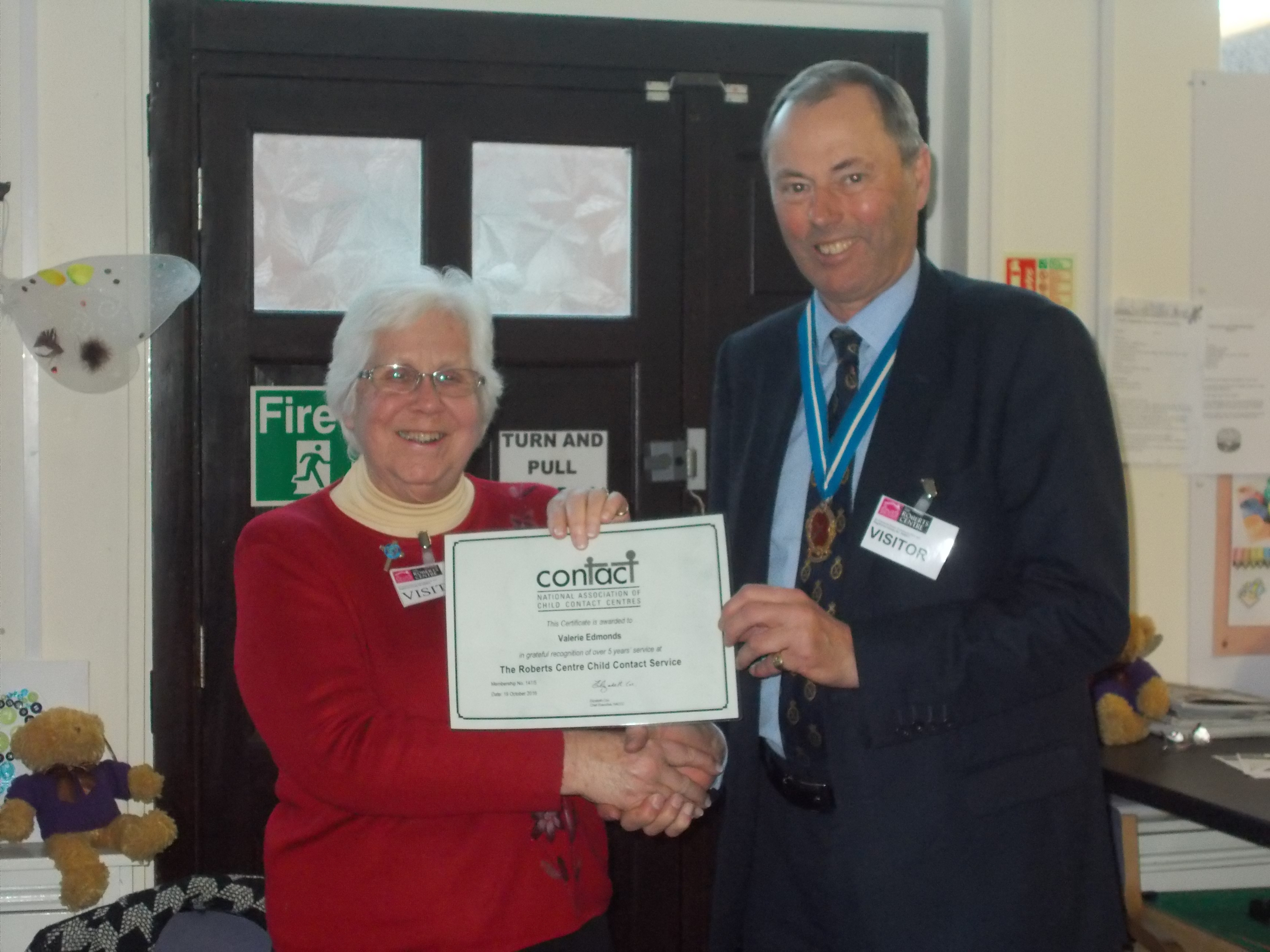 High Sherriff gives a long service certificate to Val who has volunteered at the Roberts Child Contact Centre for over 10 years.
